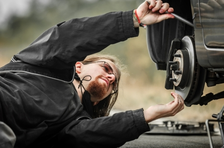 Handsome young man repairing flat tire photo