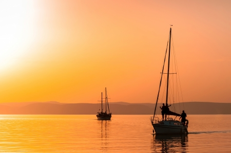 Sailing boats with a beautiful sunset at the sea photo