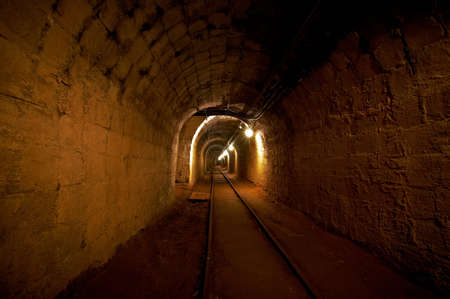 Underground mine passage with rails and light Stock Photo - 18044341