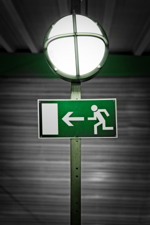 bipedal: Exit sign with industrial lamp Stock Photo