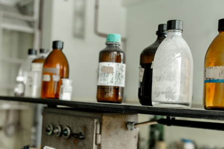 Photo of an old laboratory with a lot of bottles and dirt photo