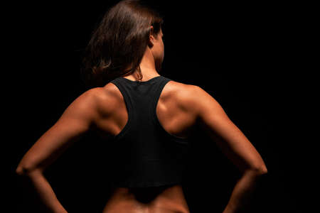 Upper body of a muscular woman from the back in a studio photo