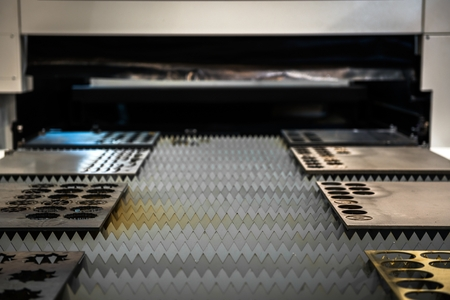 Laser cutter cutting metal plates in a factory photo