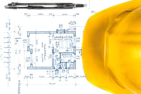 interior desing: Yellow helmet of an engineer with plans and bow Stock Photo
