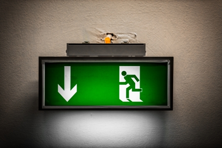 Exit sign on the wall in a building photo
