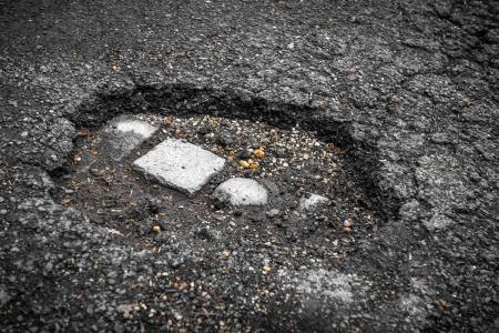 Tarmac road with big holes in Belgium Stock Photo - 24136211