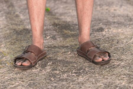 foot ware: Feet of a sad farmer without crop