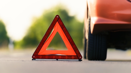 roadside assistance: Red triangle of a car on the road Stock Photo