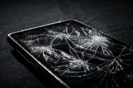 Smartphone with broken screen on dark