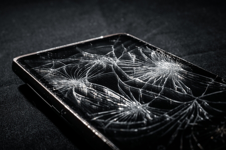 broken telephone: Smartphone with broken screen on dark