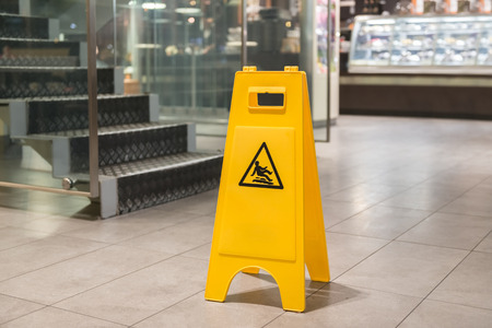 Yellow sign that alerts for wet floor photo