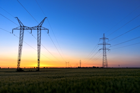 Tall power lines at dusk with blue sky photo