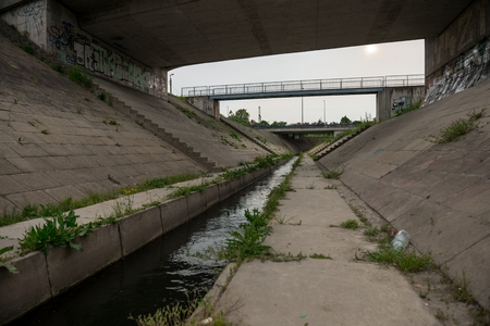 Sewage canal outdoors with dirty water flowing