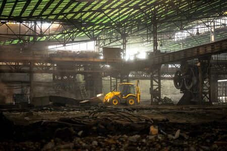 Large industrial interior with yellow bulldozer inside photo