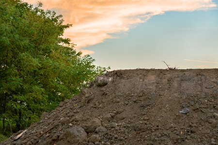 Large pile of soil under blue sky and trees photo