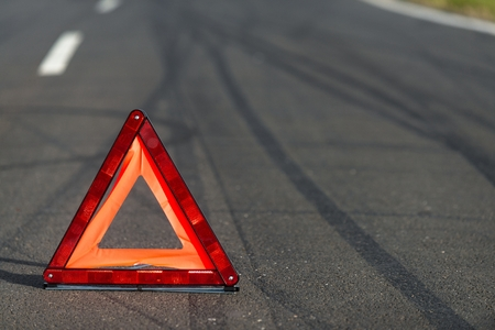 damaged car: Red triangle of a car on the road Stock Photo