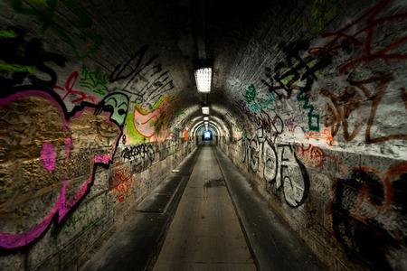 Donkere en lange undergorund passage met licht Stockfoto