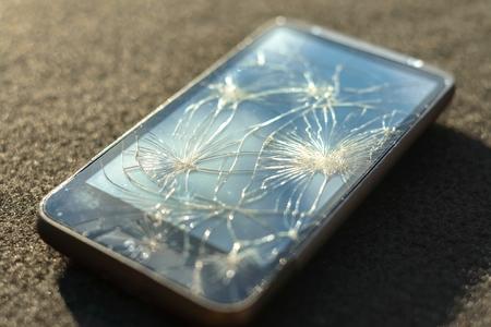 Smartphone with broken screen on dark background photo