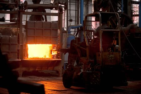 ironworks: Hot iron in smeltery held by a worker