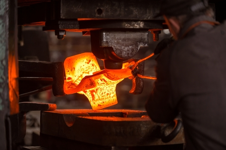 Hot iron in smeltery held by a worker