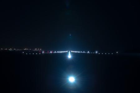 夜の空港の滑走路で着陸灯
