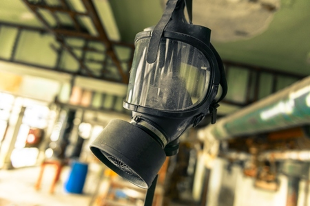 chemical warfare: Gasmask hanging from cieling in abandoned interior