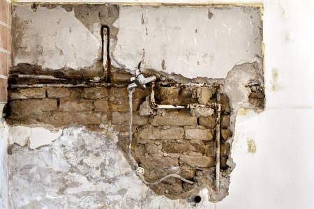 Damaged wall plumbing in a house closeup 스톡 콘텐츠