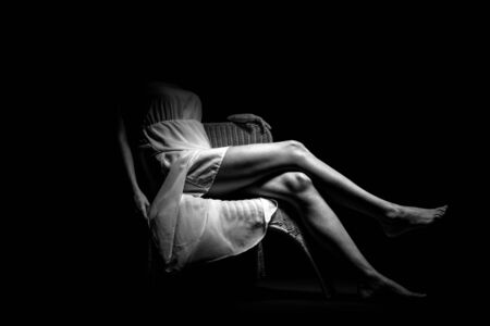 Woman sitting in a chair showing her legs photo