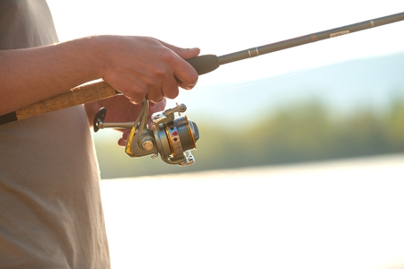 tench: Modern clean fishing rod in hands ourdoors