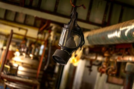 Gasmask hanging from cieling in abandoned interior photo