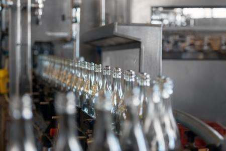 工場でベルトコンベアで多くのボトル 写真素材