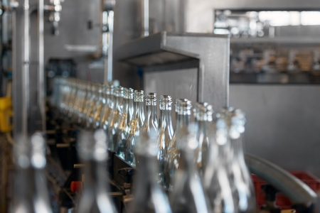 Many bottles on conveyor belt in factory Stock Photo