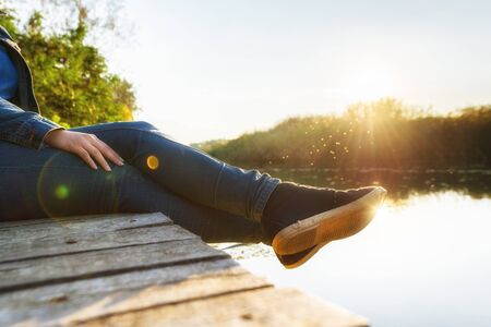 foot gear: Woman relaxing on jetty at evening hours