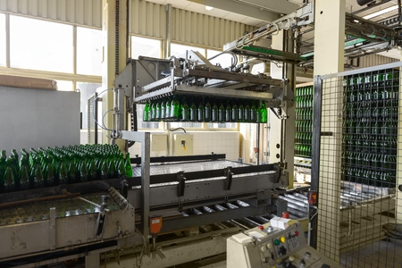 bottling: Bottling machine with many bottles in the factory