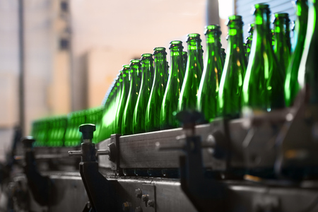 food drink industry: Many bottles on conveyor belt in factory Stock Photo