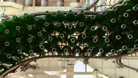 Molte bottiglie sul nastro trasportatore in fabbrica Archivio Fotografico - 40817481