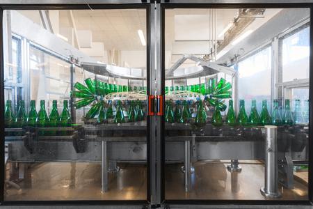 bottling: Bottling machine with many bottles in the factory