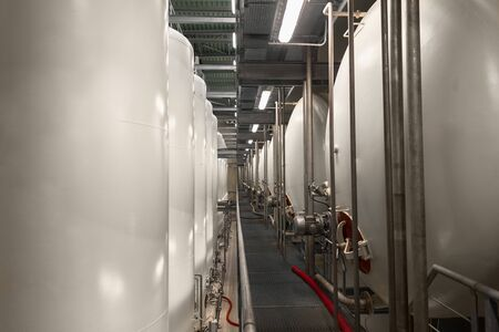 containment: Large industrial white silos in modern factory interior