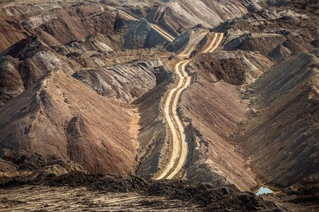goldmine: Large excavation site with roads ahead at day