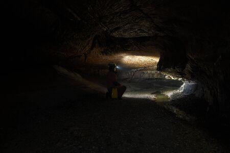 headlamp: Woman with headlamp inside cave