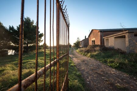 barbed wire fence: Abandoned houses with large opened gate