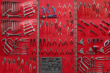 Professional work tools hanging on steel wall as background