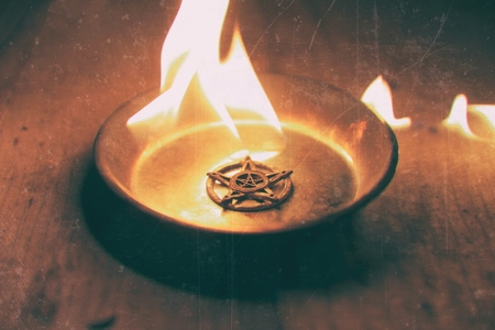 Old pentagram burning in flames close-up photo
