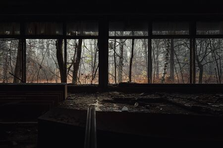 Abandoned building interior with autumnal forest outside Stock Photo