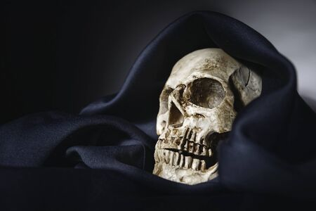 Closeup photo an old skull covered in black robe Stock Photo