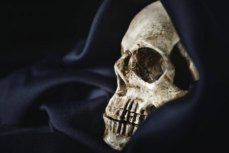 Close up photo an old skull covered in black robe