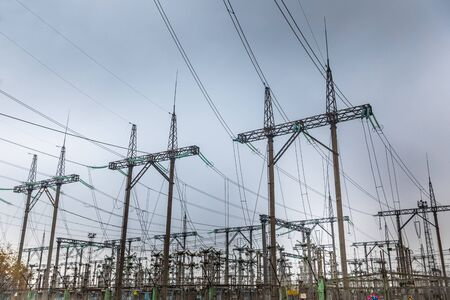 Large pylons at power distributing station under blue sky