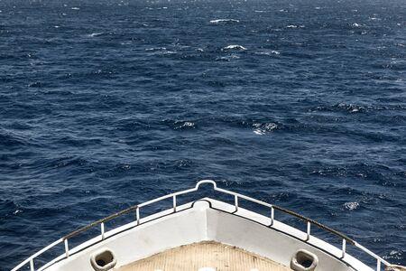 Boat heading towards the horizon with large waves Reklamní fotografie
