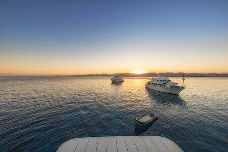 Luxury yacht docking near coral reef aerial shot