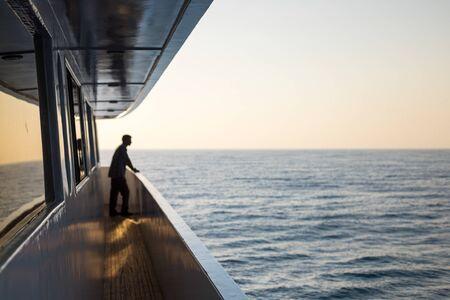 Man on Corridor of luxury yacht with ocean and horizon Reklamní fotografie